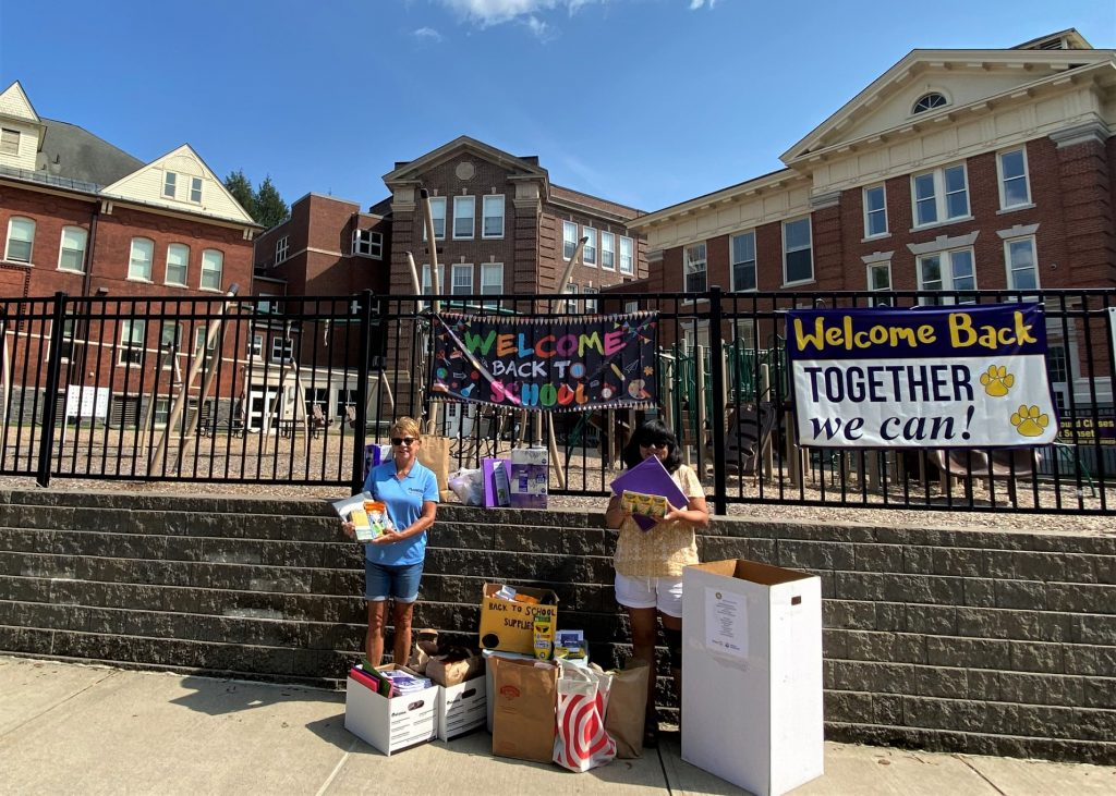 rotarians holding school supplies